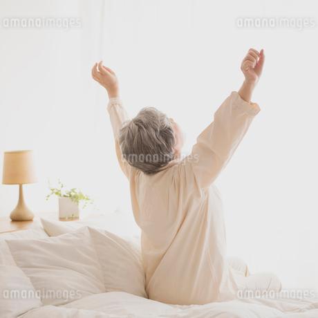 ベッドで伸びをするシニア女性の後姿の写真素材 [FYI02849900]