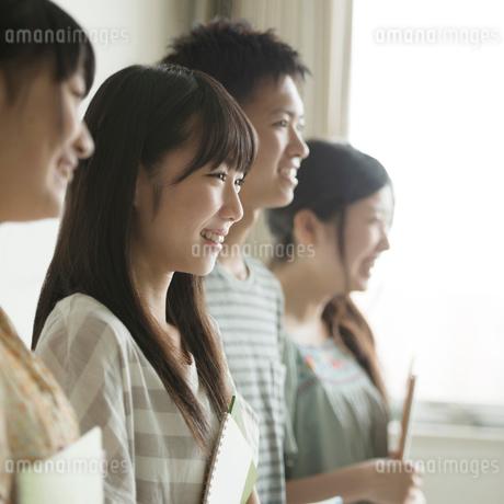 勉強道具を持ち微笑む学生の写真素材 [FYI02849901]