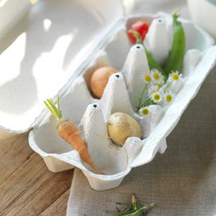 卵のケースに入ったミニ野菜と野花の写真素材 [FYI02849913]