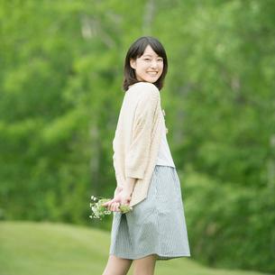 野花を持ち微笑む女性の写真素材 [FYI02849950]