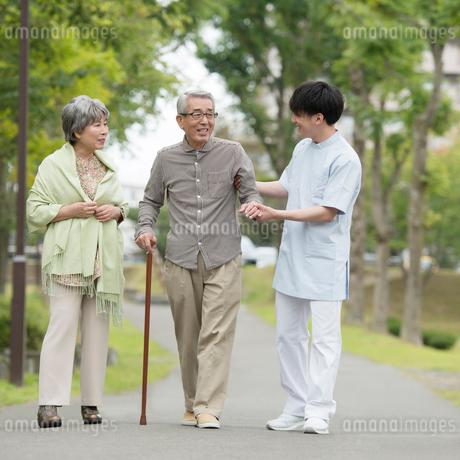 シニア男性を支える介護士と見守る妻の写真素材 [FYI02849951]