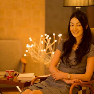 椅子に座り微笑む女性のポートレートの写真素材 [FYI02849952]