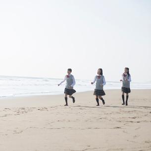 砂浜を走る女子校生の写真素材 [FYI02849954]