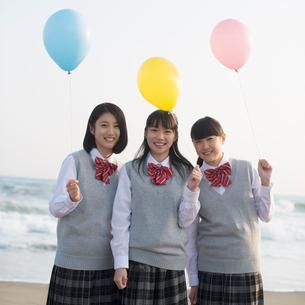 砂浜で風船を持ち微笑む女子校生の写真素材 [FYI02849965]