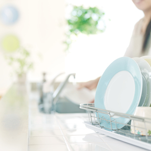 キッチンの水切りカゴに置いてある食器と食器を洗う女性の写真素材 [FYI02849994]