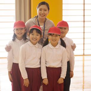 体育館で微笑む先生と小学生の写真素材 [FYI02850091]