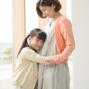 母親のお腹に耳をあてる女の子の写真素材 [FYI02850103]