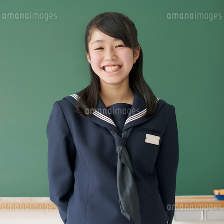 黒板の前で微笑む女子学生の写真素材 [FYI02850105]