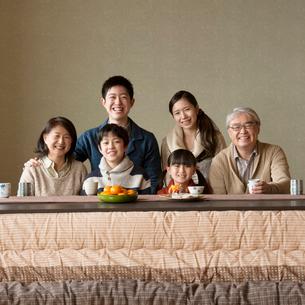 こたつで微笑む3世代家族の写真素材 [FYI02850131]