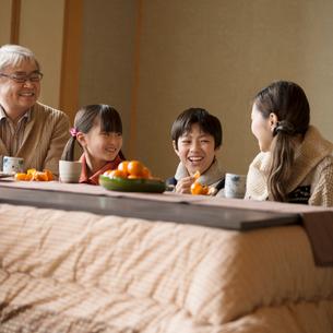 こたつで談笑をする3世代家族の写真素材 [FYI02850142]