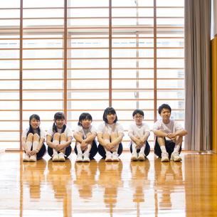 体育館で体育座りをする学生の写真素材 [FYI02850157]
