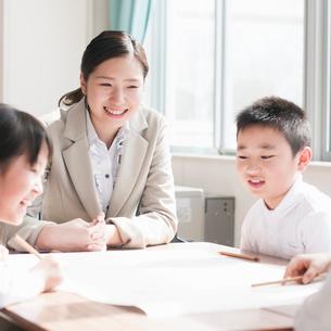 グループ学習をする小学生と先生の写真素材 [FYI02850172]