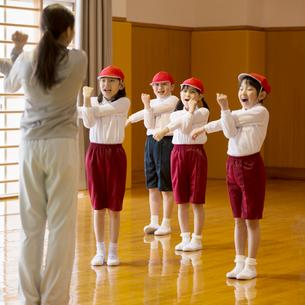 体育館で準備運動をする小学生と先生の写真素材 [FYI02850188]
