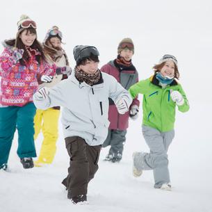 雪原を走る若者たちの写真素材 [FYI02850194]