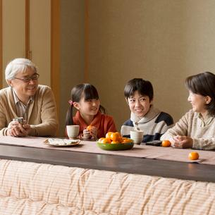 こたつで談笑をする祖父母と孫の写真素材 [FYI02850196]