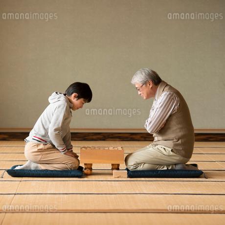 和室で将棋をする祖父と孫の写真素材 [FYI02850200]