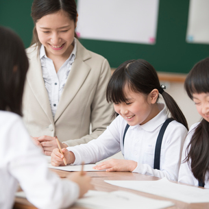 グループ学習をする小学生と先生の写真素材 [FYI02850201]