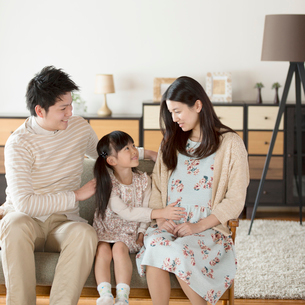 ソファーに座り談笑をする家族の写真素材 [FYI02850206]