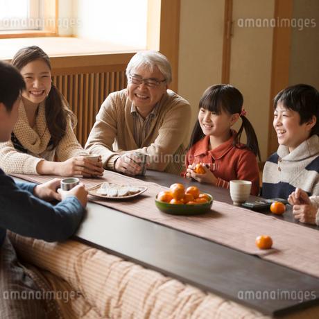 こたつで談笑をする3世代家族の写真素材 [FYI02850229]