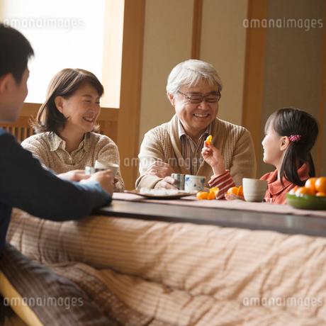 こたつで談笑をする3世代家族の写真素材 [FYI02850233]