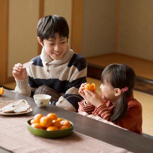 こたつで干し芋とみかんを食べる兄妹の写真素材 [FYI02850234]