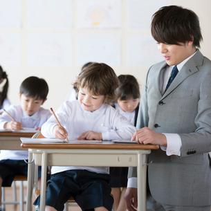 先生に勉強を教わる小学生の写真素材 [FYI02850246]