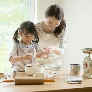 キッチンでお菓子作りをする親子の写真素材 [FYI02850269]