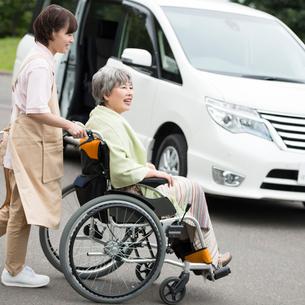 シニア女性の乗る車椅子を押すホームヘルパーの写真素材 [FYI02850272]