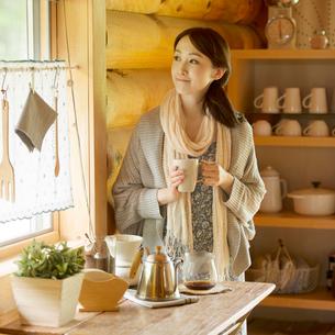 コーヒーカップを持ち窓の外を眺める女性の写真素材 [FYI02850277]