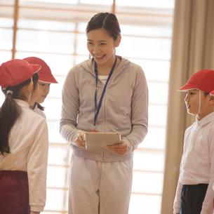 体育館で話をする先生と小学生の写真素材 [FYI02850280]