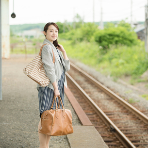 駅のホームで電車を待つ女性の写真素材 [FYI02850284]