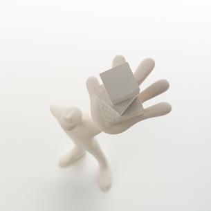 左手に重ねた箱を持って立つ人のオブジェ クラフトの写真素材 [FYI02850312]