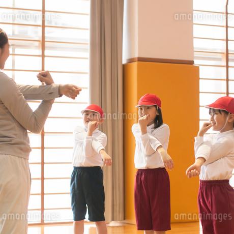 体育館で準備運動をする小学生と先生の写真素材 [FYI02850316]