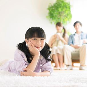 リビングで頬杖をつき微笑む女の子の写真素材 [FYI02850322]