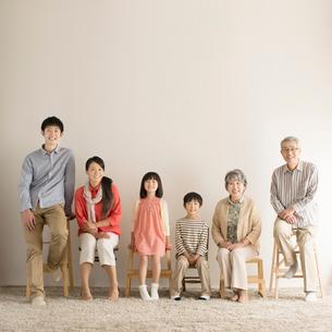椅子に座り微笑む3世代家族の写真素材 [FYI02850329]