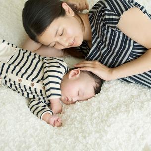眠る赤ちゃんと見守る母親の写真素材 [FYI02850339]