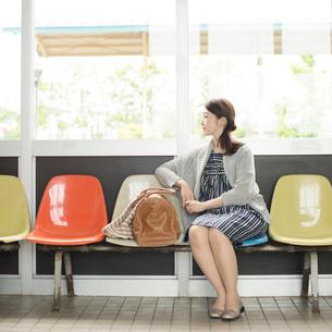 椅子に座り電車を待つ女性の写真素材 [FYI02850357]