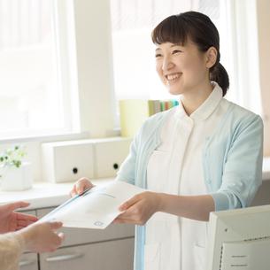 患者に薬を渡す女性職員の写真素材 [FYI02850364]