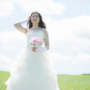 草原でブーケを持ち微笑む花嫁の写真素材 [FYI02850368]
