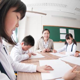 グループ学習をする小学生と先生の写真素材 [FYI02850372]
