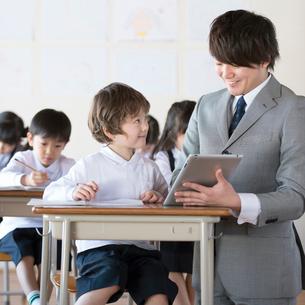 先生に勉強を教わる小学生の写真素材 [FYI02850417]