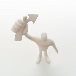 右手に矢印を掲げて立つ人のオブジェ クラフトの写真素材 [FYI02850491]
