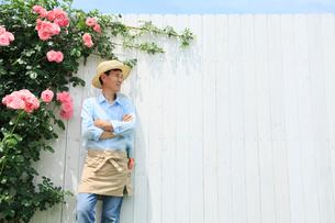 バラと白い板壁の前に立つ中年男性の写真素材 [FYI02850525]