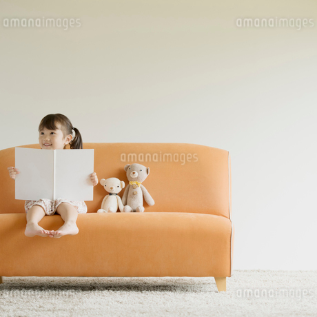 ソファーに座り絵本を読む女の子の写真素材 [FYI02850602]