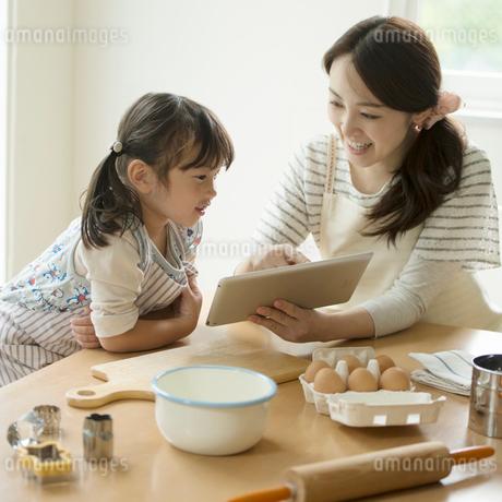 タブレットPCでレシピを調べる親子の写真素材 [FYI02850628]
