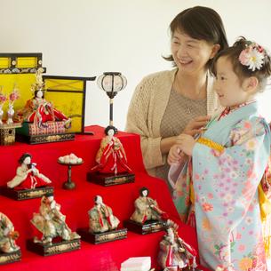 孫と一緒に雛人形を見る祖母の写真素材 [FYI02850636]