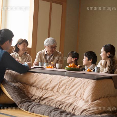 こたつで談笑をする3世代家族の写真素材 [FYI02850944]