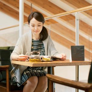 カフェで雑誌を見る女性の写真素材 [FYI02851029]