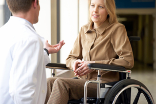Wheelchair-bound woman talking to doctorの写真素材 [FYI02851063]