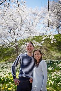 桜咲く公園に立つ外国人カップルの写真素材 [FYI02851269]